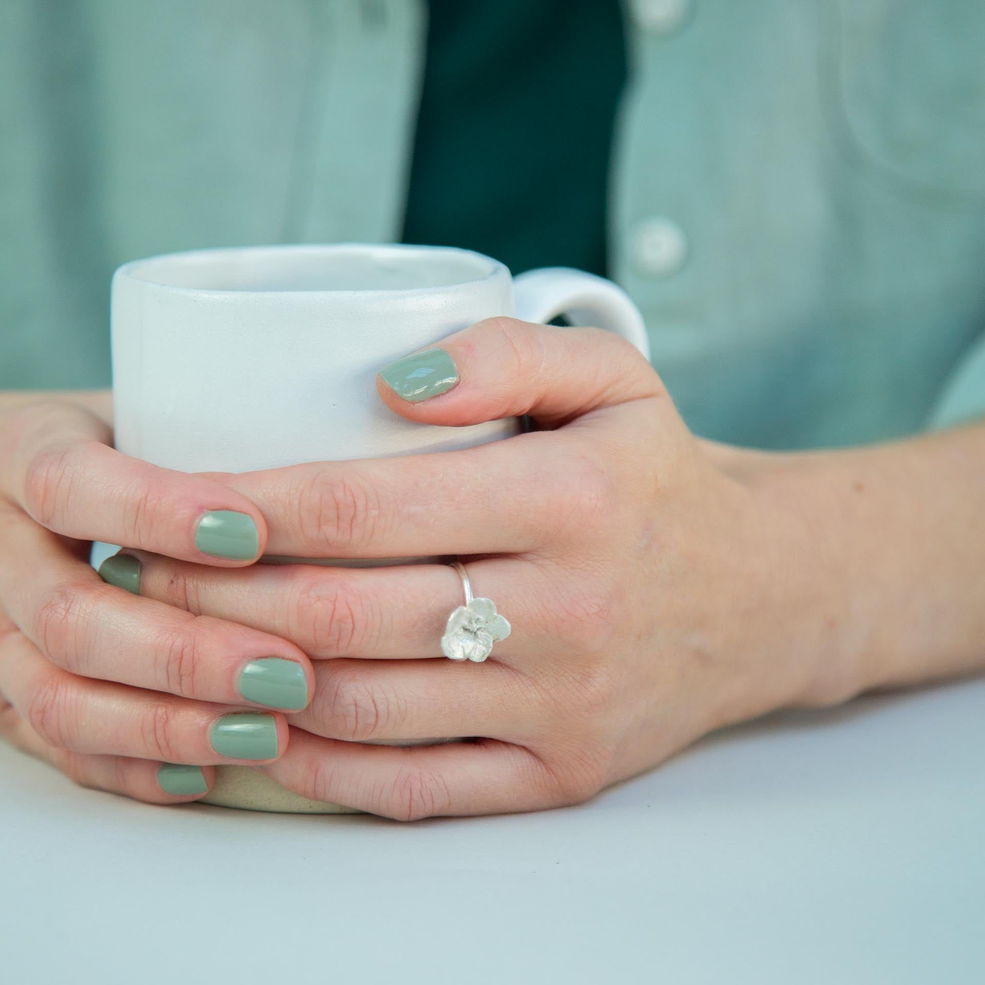 hands holding mug with silver flower ring