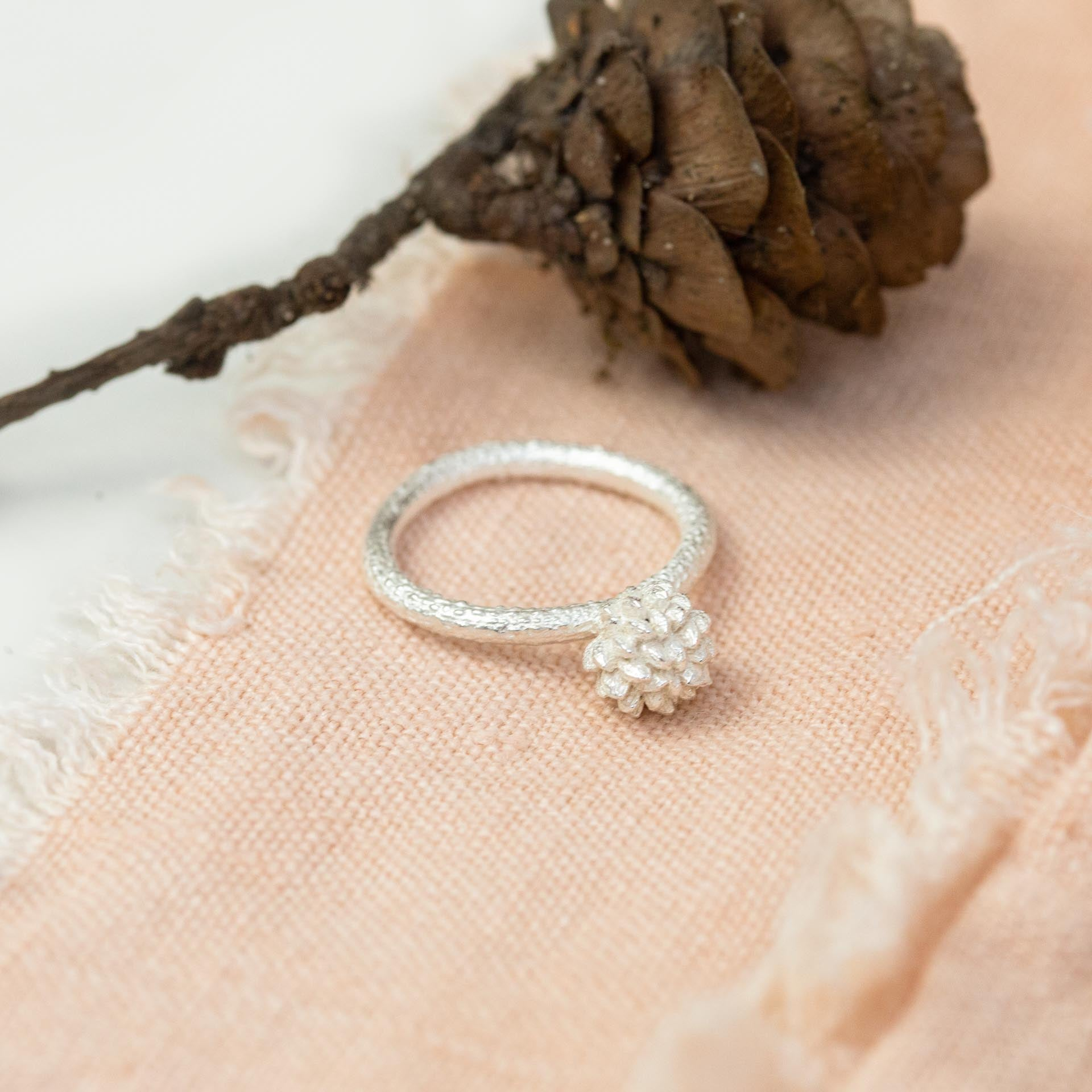 silver buttercup ring on pink cloth near pine cone