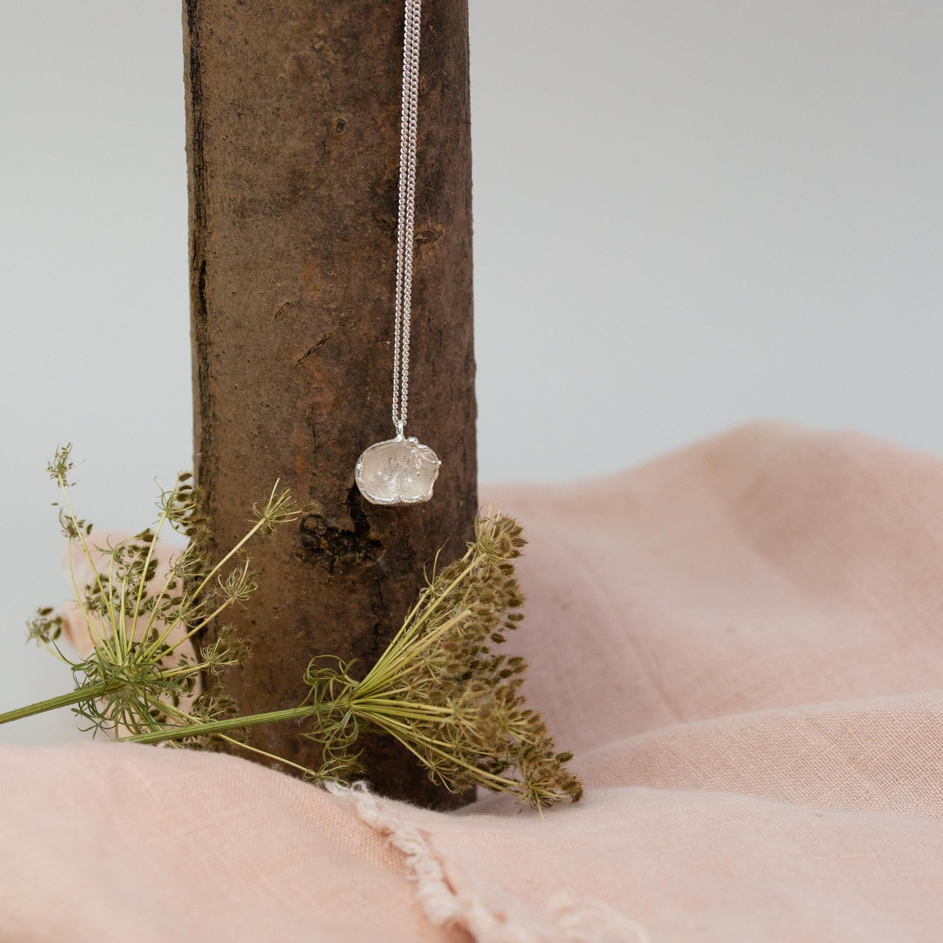 silver hazelnut necklace hanging from branch above dried flowers and pink cloth