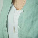silver foxglove pendant necklace on model hanging above a green shirt and white t-shirt