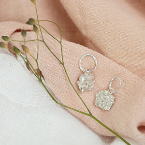 silver Hedgerow Flower Drop Hoop Earrings on pink cloth next to dried flowers