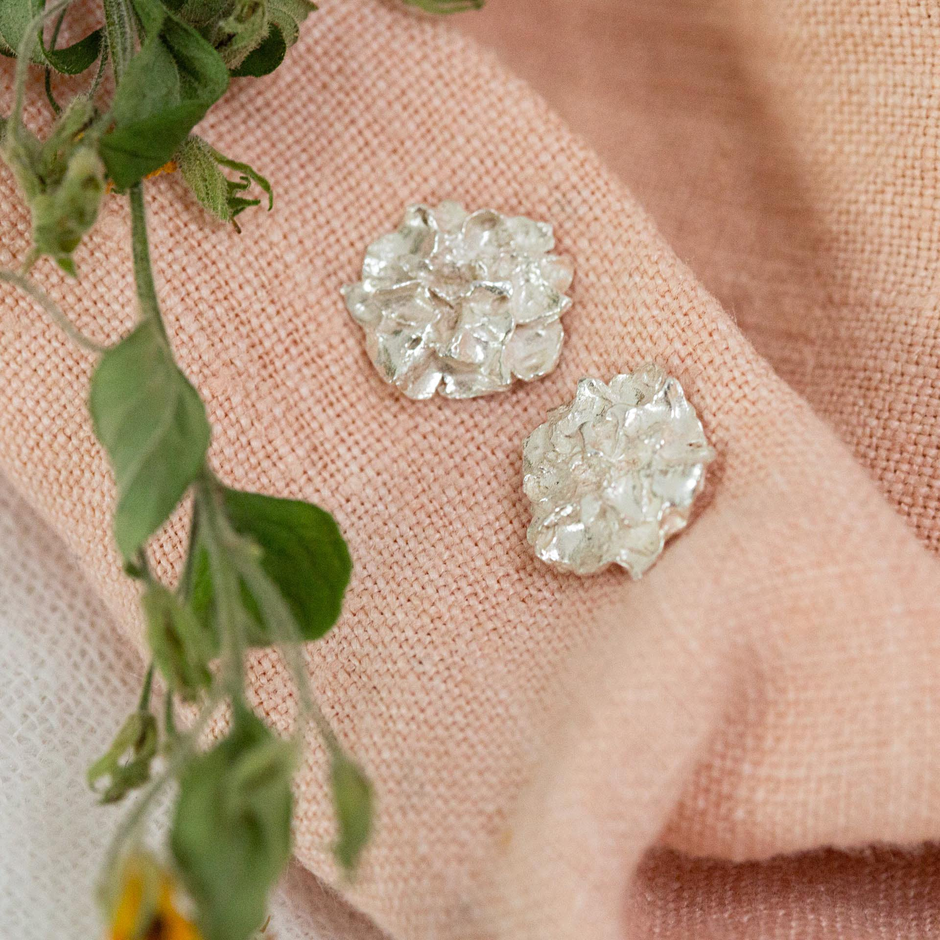 Silver Hedgerow Flower stud earrings on pink cloth next to dried flower