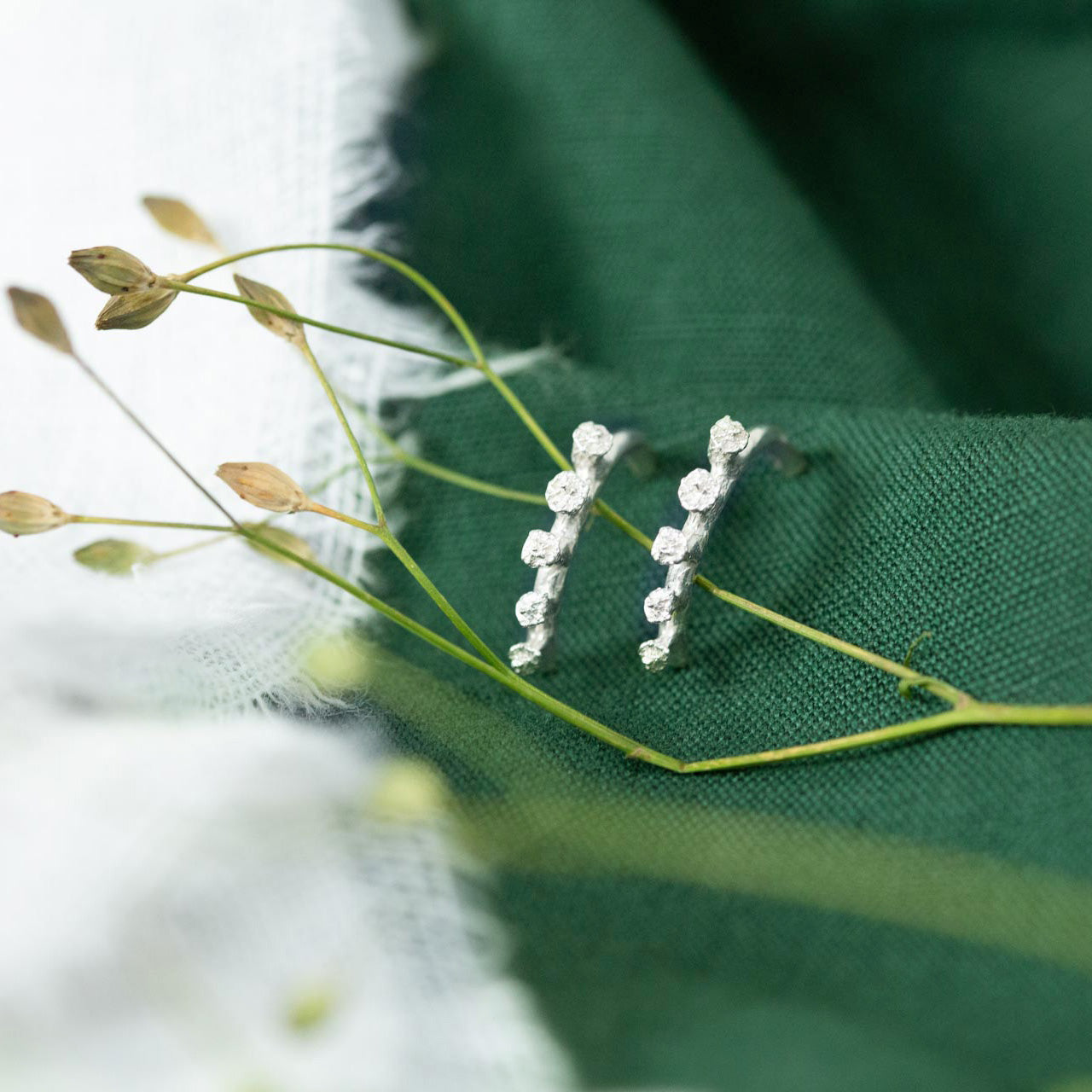 Silver Ivy bud half hoop earrings resting on green and white cloth with dried flowers in the foreground