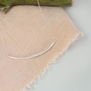 silver smooth twig necklace on pink cloth near wooden branch