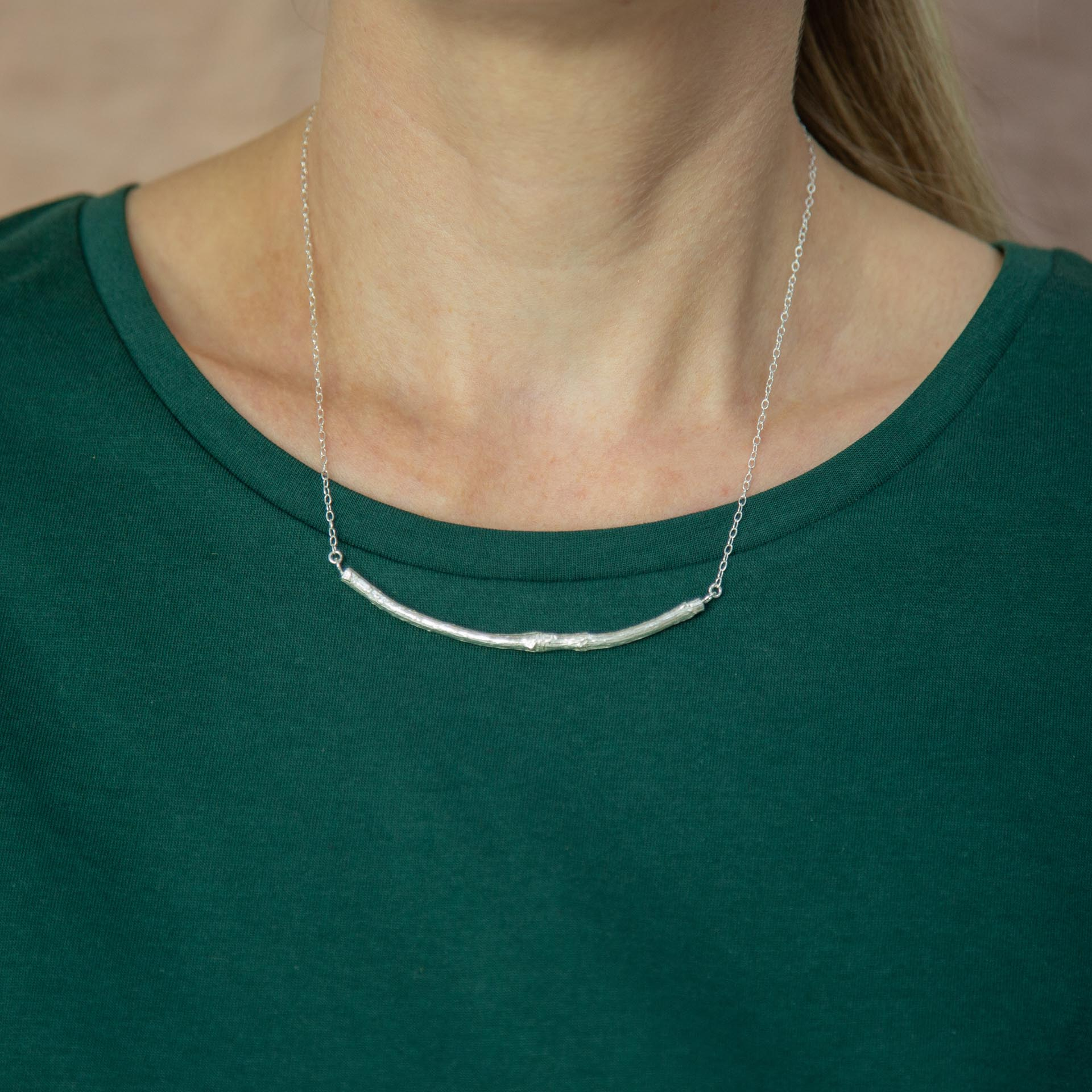 silver smooth twig necklace modelled around neck resting on green t-shirt