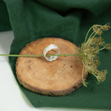 silver Snow Drop Leaf Wrap Ring on wood next to green cloth and dried flora