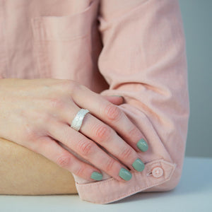 Snow Drop Leaf Wrap Ring modelled on hand resting on arm with pink shirt