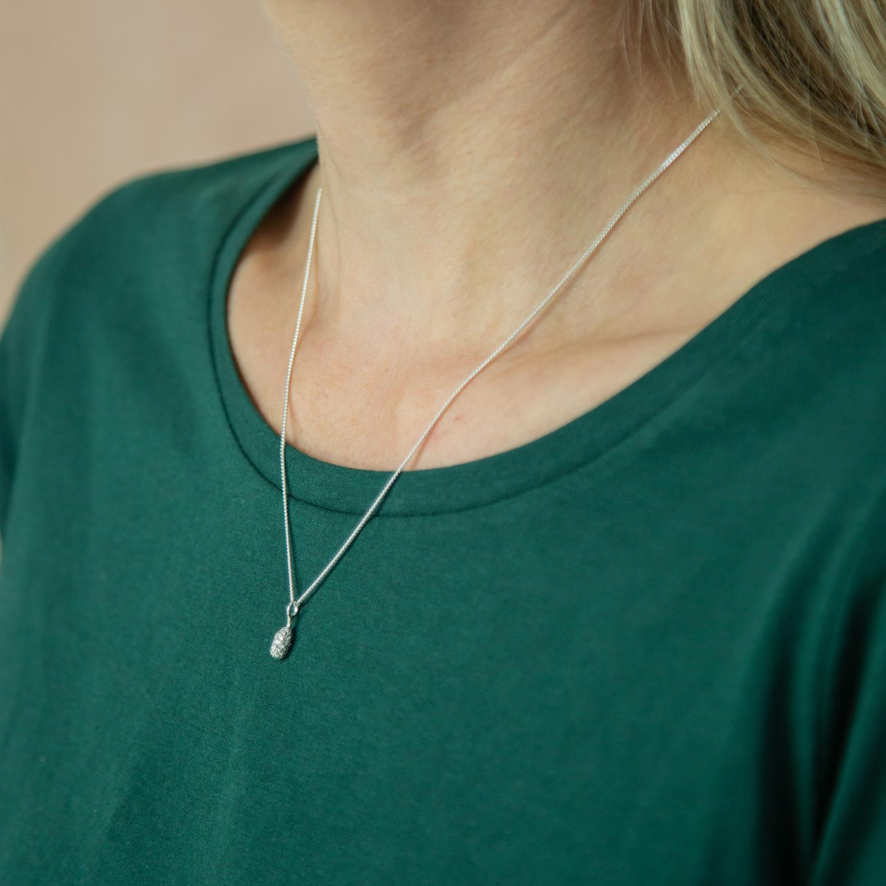 silver Spruce Drop Pendant modelled around neck on green t-shirt