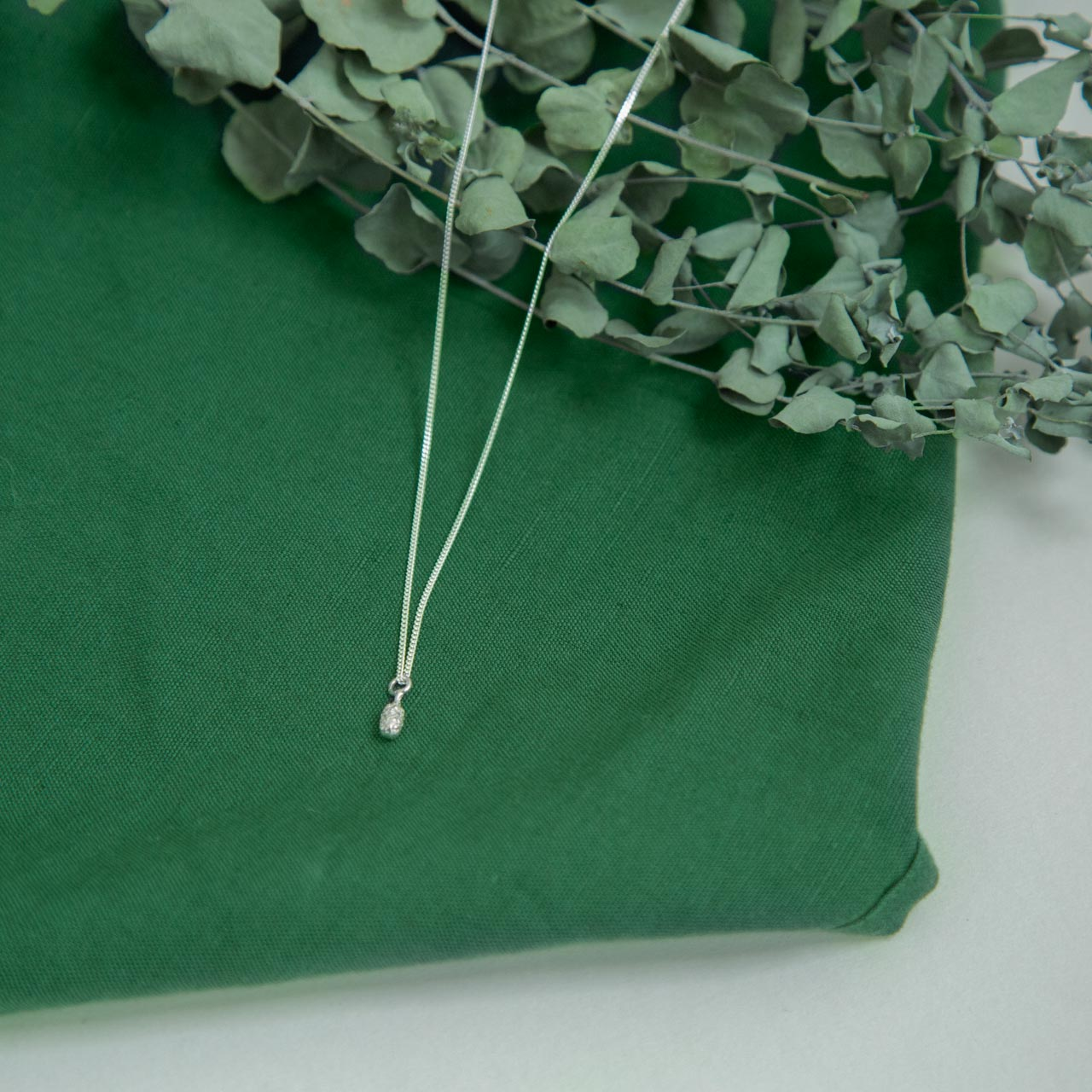 silver Spruce Drop Pendant on green cloth near dried flora