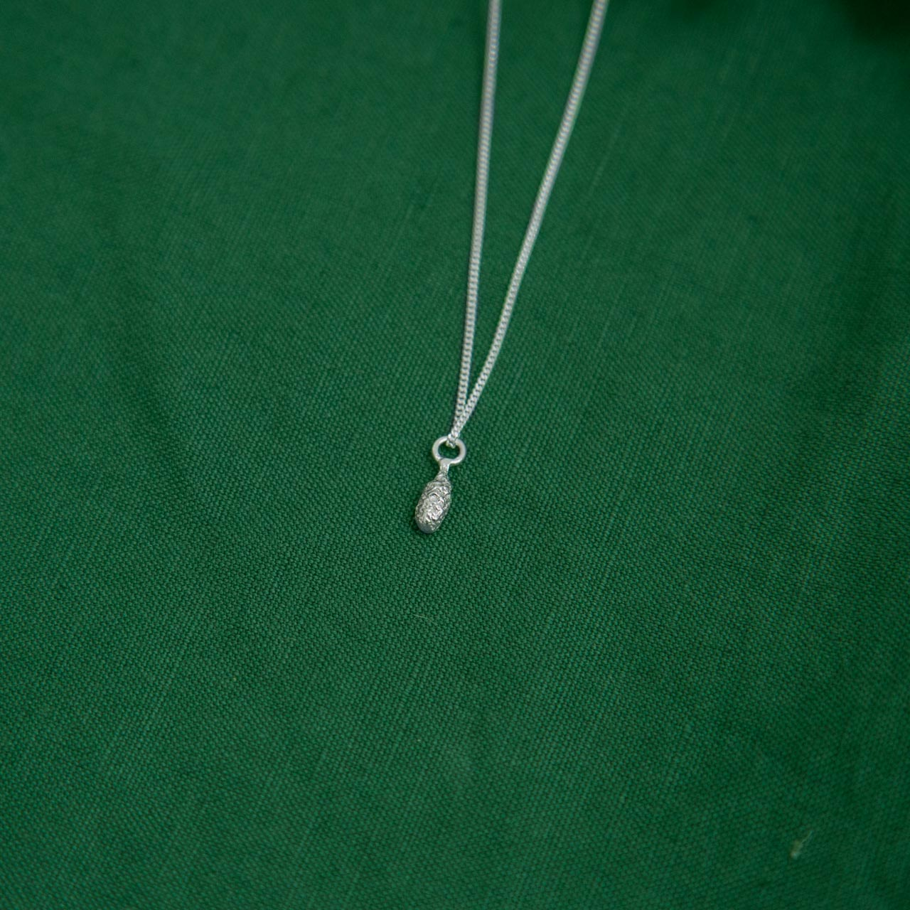 silver Spruce Drop Pendant on green cloth