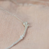 Silver Textured Twig Necklace on pink cloth