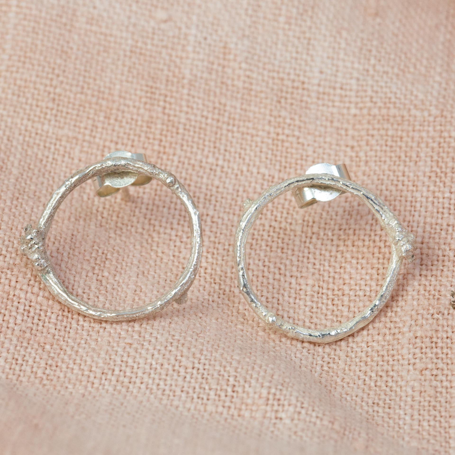 Silver Twig Circle Stud Earrings on stem pink cloth