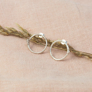 Silver Twig Circle Stud Earrings on stem next to pink cloth