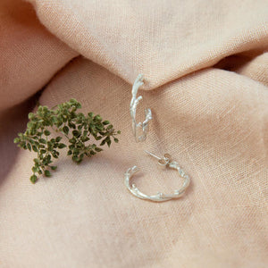 Silver Twisted Twig Hoops on pink cloth near flora