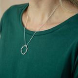 silver wreath pendant modelled around neck on green t-shirt