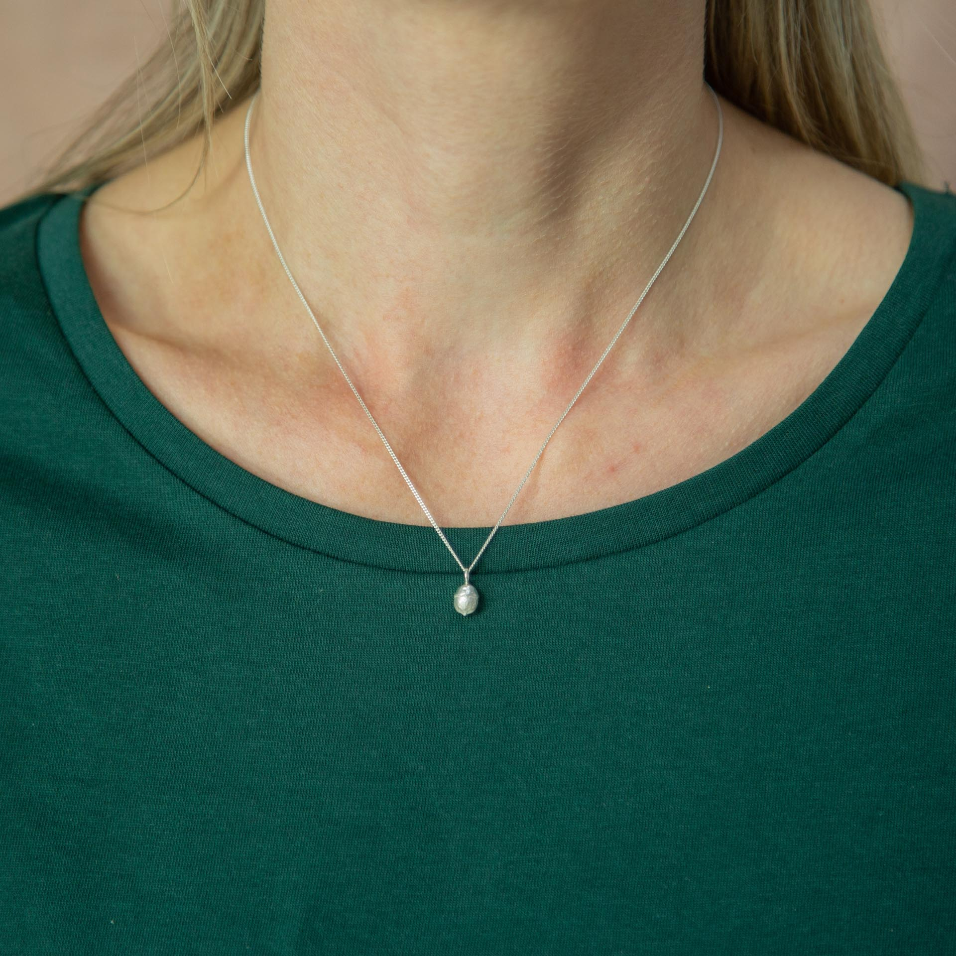 yew berry silver necklace modelled around neck on green tshirt