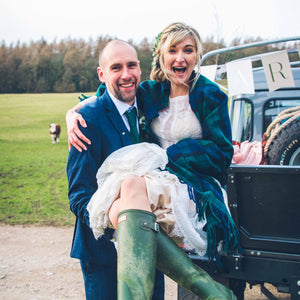 husband carrying wife. She is wearing a wedding dress and green wellington boots.