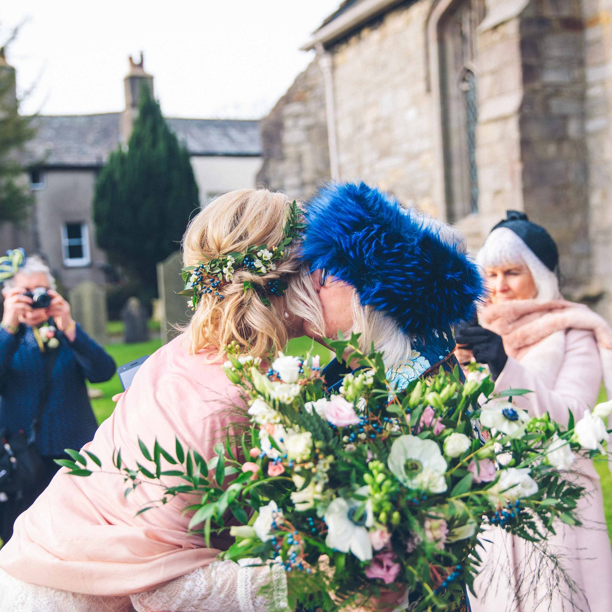 an embrace at a wedding with a large bouquet of flowers
