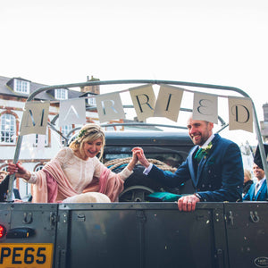 bride and groom in vehicle below 'married' sign