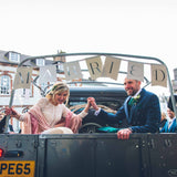 husband and wife in landrover trailer with married lettering above them