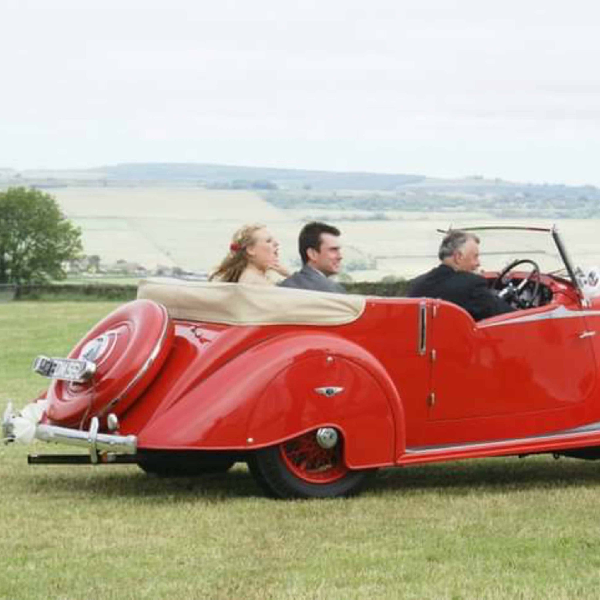 red wedding car with passangers in field