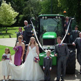 wedding party in front of green tractor