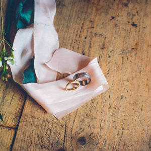 gold and silver wedding rings resting on pink cloth above wooden boards