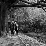 Black and white of mum and daughter walking in the woods with dog