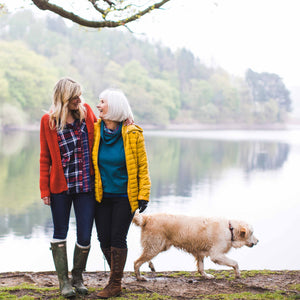 mother and daughter laughing near lake with dog