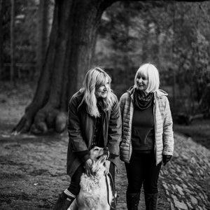 black and white image of mother and daughter walking with dog