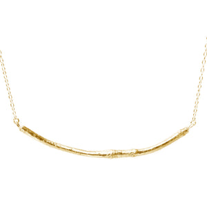 gold smooth twig necklace on white background