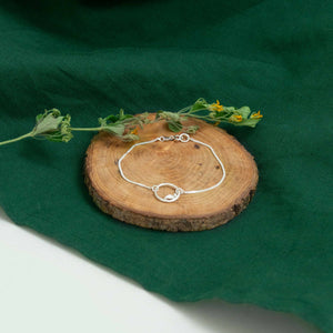 silver eternity bracelet on wood above green cloth