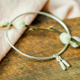 silver catkin bangle on pink cloth and wood