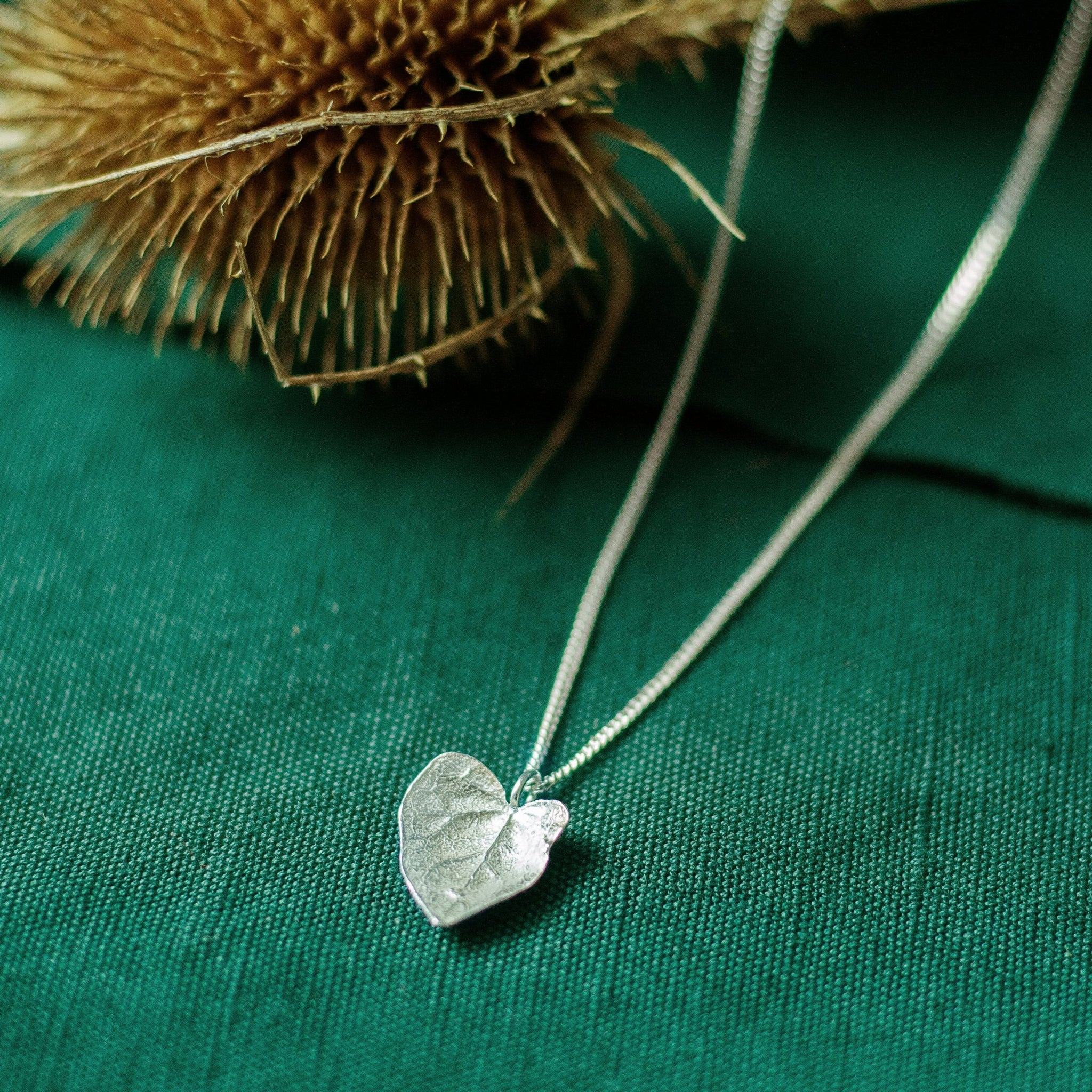silver ivy leaf necklace on green background with dried flower