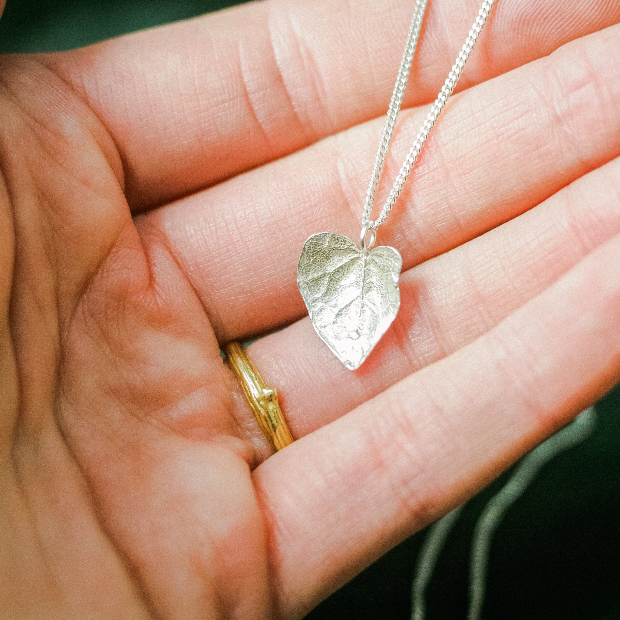 ivy leaf silver necklace held in hand