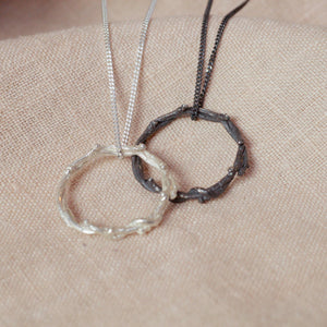 silver wreath pendant next to oxidised wreath pendant