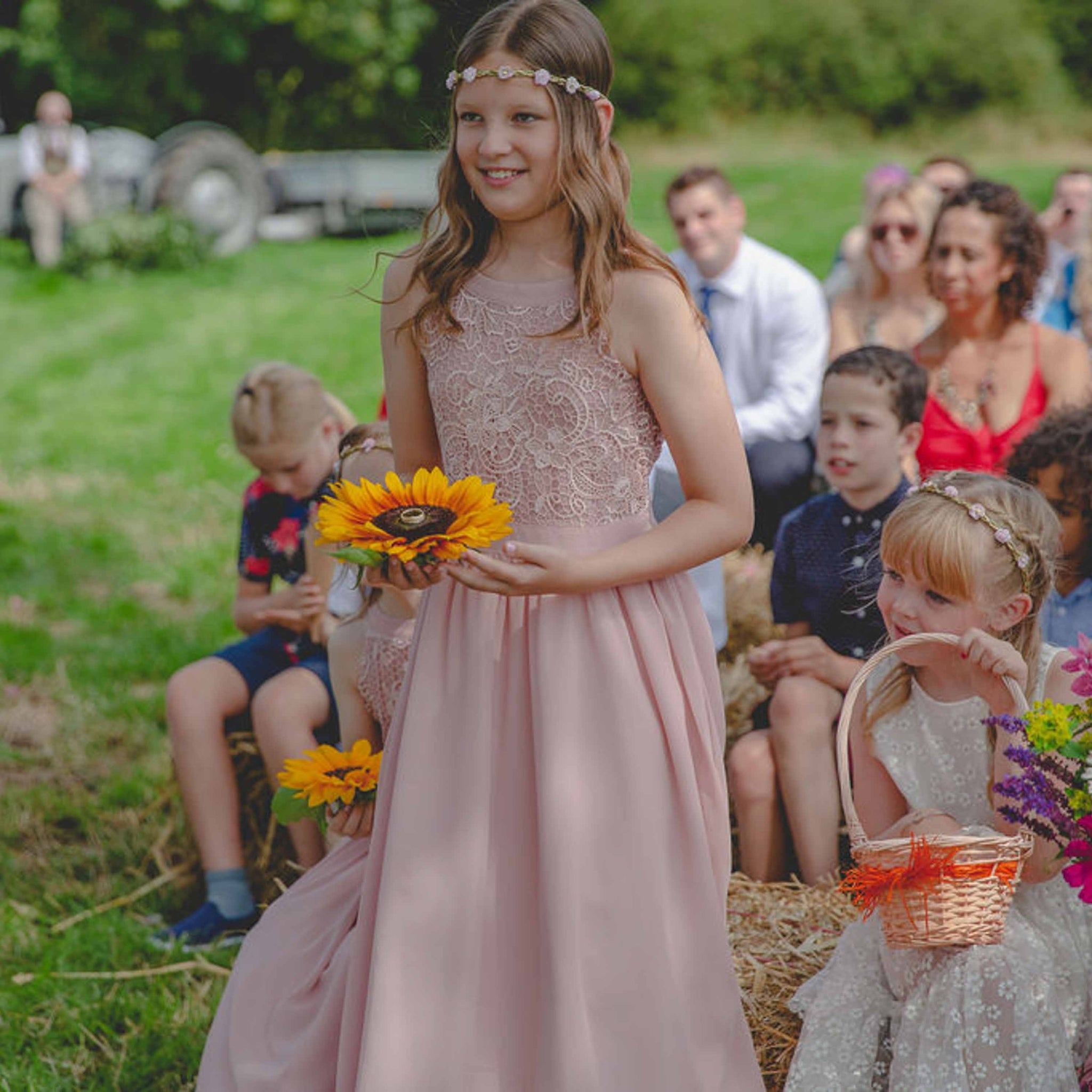 bridesmaids wearing pink dresses in outdoor wedding carrying rings on a sunflower