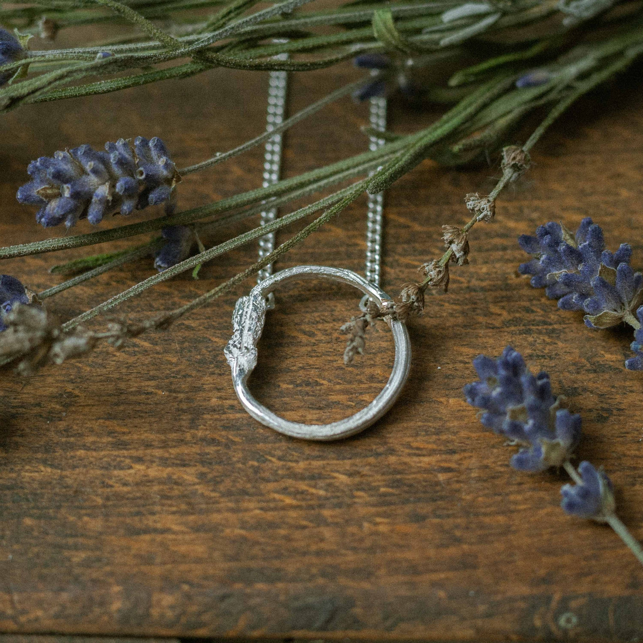 single eternity pendant on wood surrounded by dried flowers