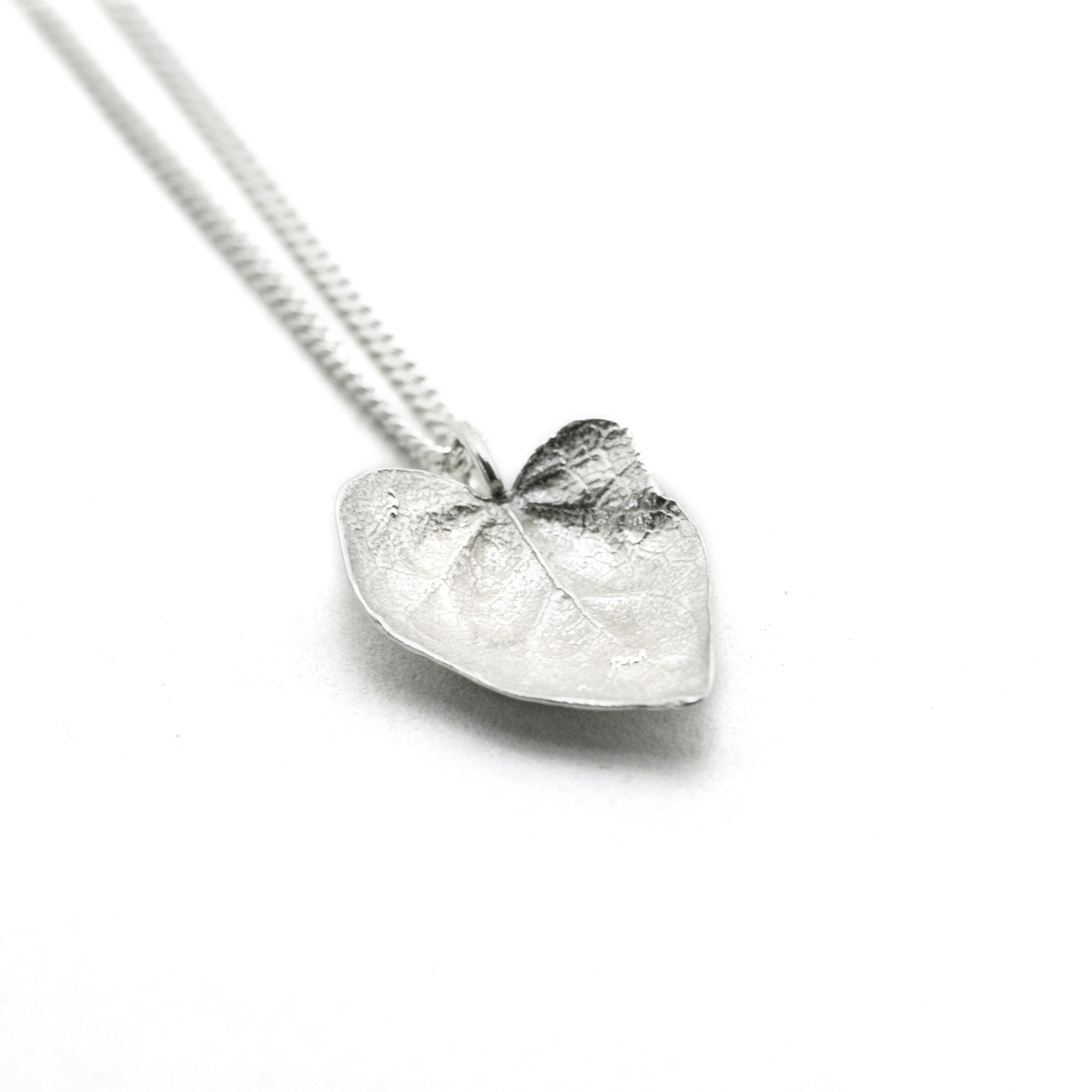 silver ivy leaf necklace on white background