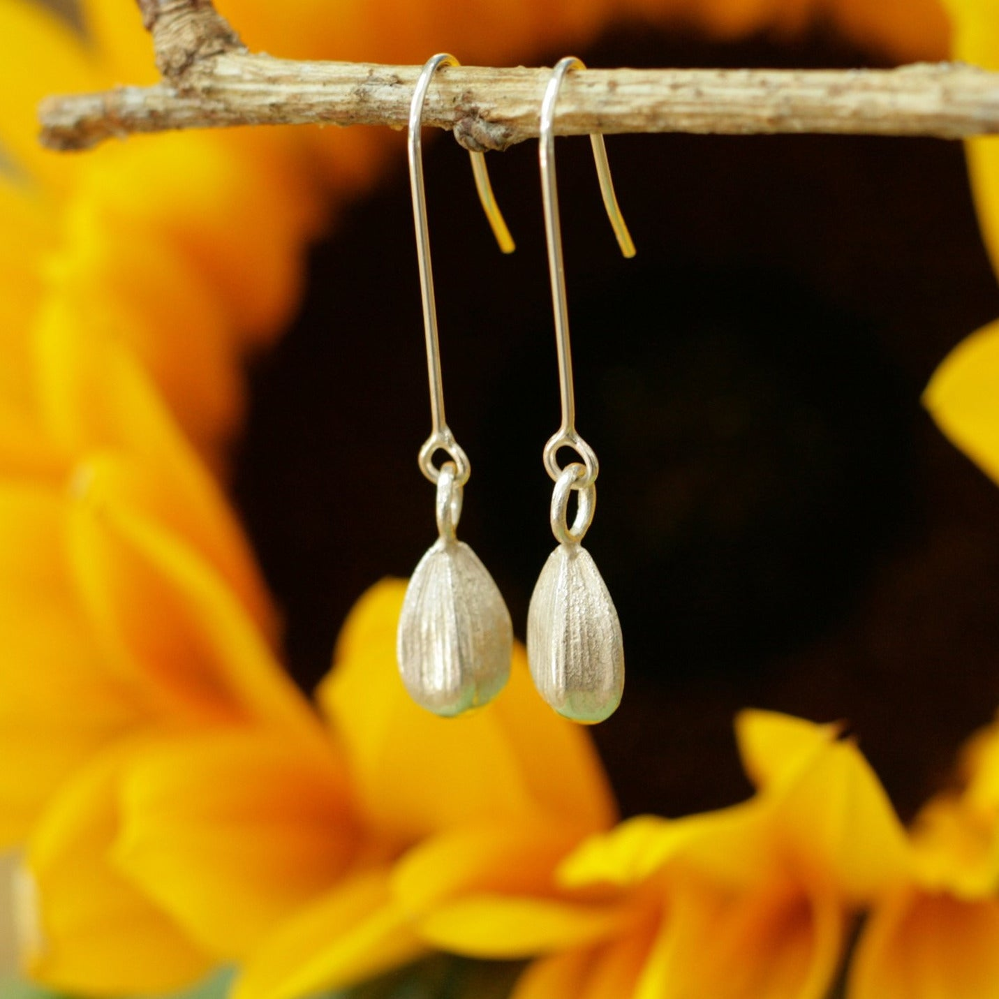 Cast sunflower seed danngly earrings hand made in silver photographed in front of sunflower