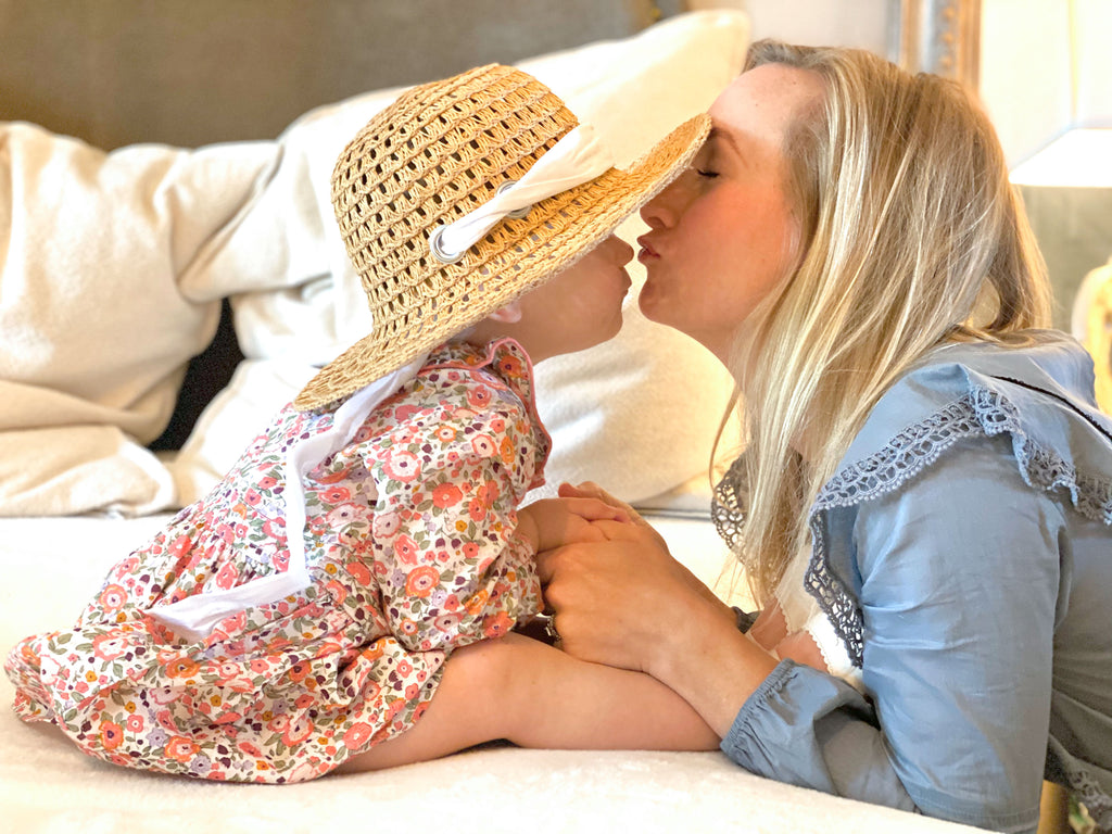Blonde woman in a blue flutter sleeve dress with lace insert kissing her daughter. Her daughter is wearing a straw hat and a mini floral printed pink dress.