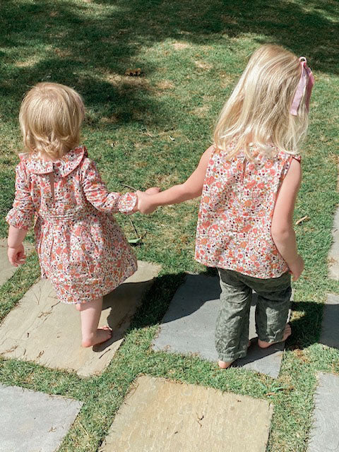 Two little girls holding hands walking in floral printed outfits.