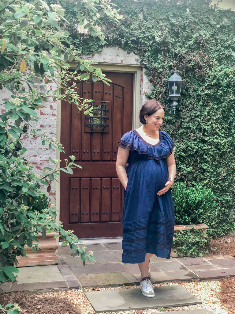 Woman expecting a baby wearing a navy dress with black lace inserts and sneakers by her front door.