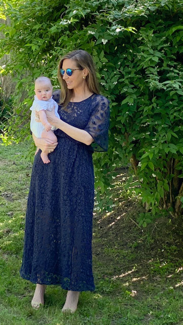 Woman in sunglasses holding a baby in her yard. Woman is wearing a navy embroidered dress.