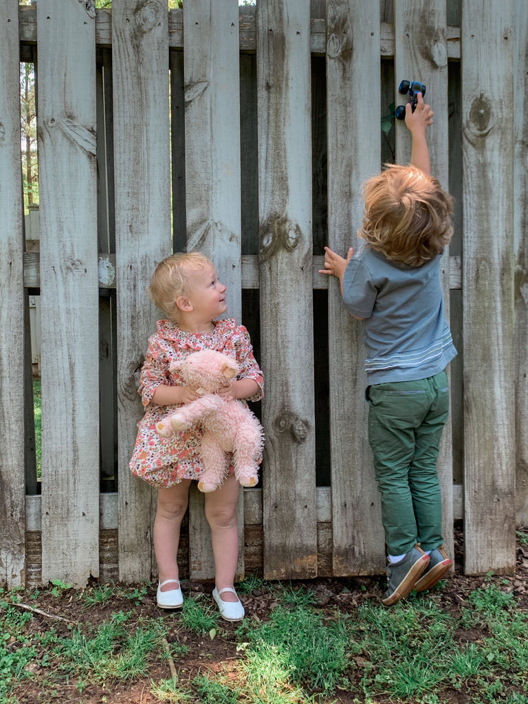 LIttle girl holding a pink stuffed animal with her back to a fence is wearing a pink mini floral dress while her brother drives his car up the fence while wearing a blue embroidered t-shirt and green pants.