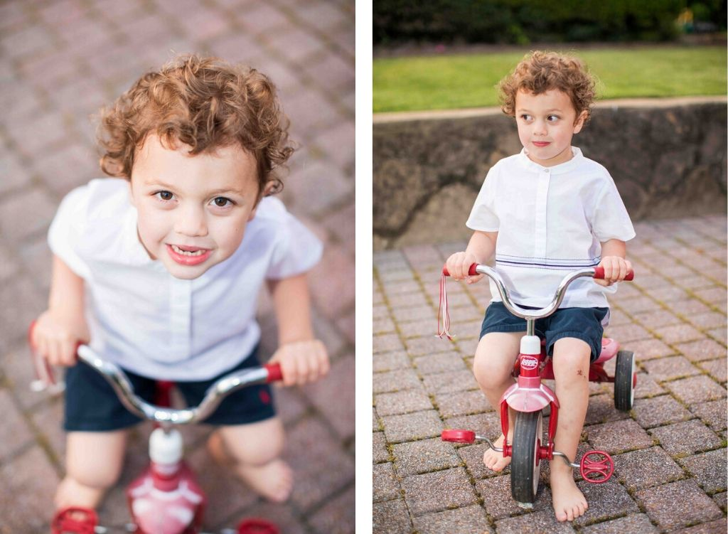 Two images of a little boy on a tricycle. He has curly brown hair and is wearing a white button down popover with blue embroidery and navy shorts.
