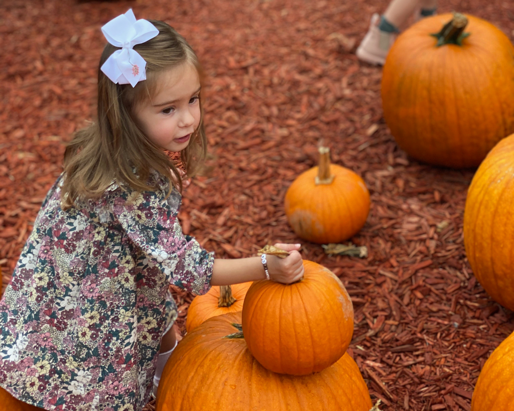 Child in floral dress at pumpkin patch