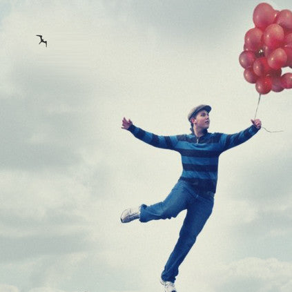 Boy flying away with red helium balloons into the air