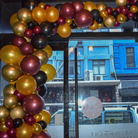 Burgundy and gold organic balloon garland inside The Establishment venue on Courtney Place