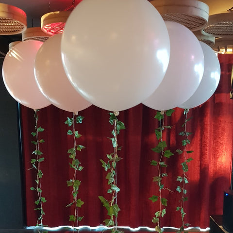 White helium balloon decorations with ivy inside of QT hotel in Wellington